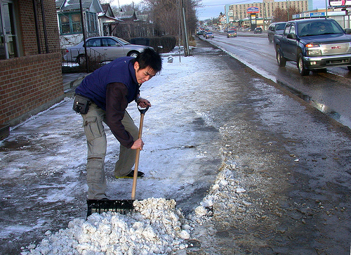 shoveling snow in front of a store