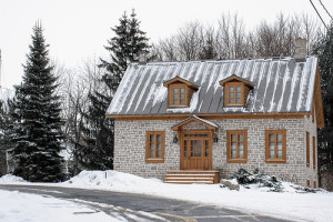 stone home covered in snow